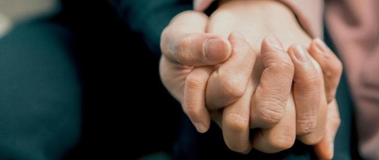 splecione dłonie dwóch osób
