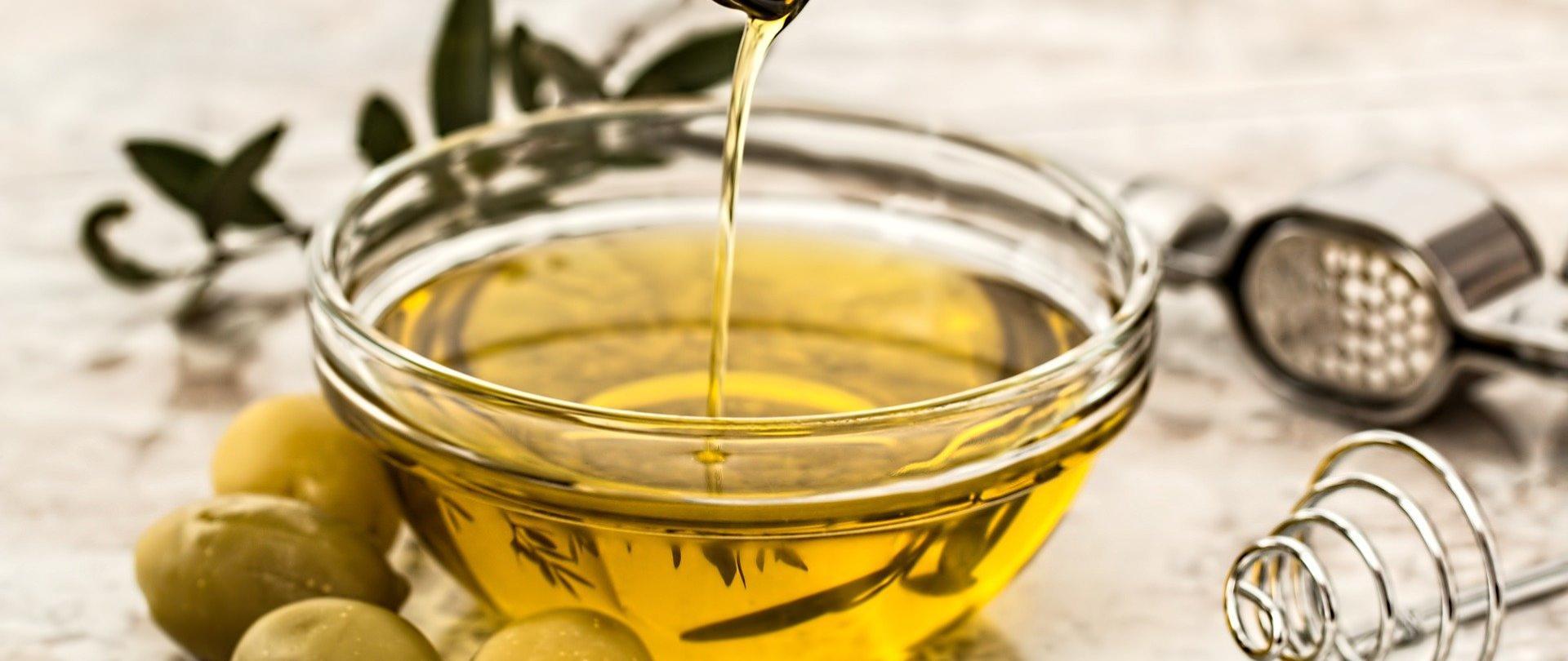 Na zdjęciu znajduje się miska z oliwą z oliwek i gałązką rozmarynu. Obok miski leżą cztery oliwki, wyciskacz do czosnku.