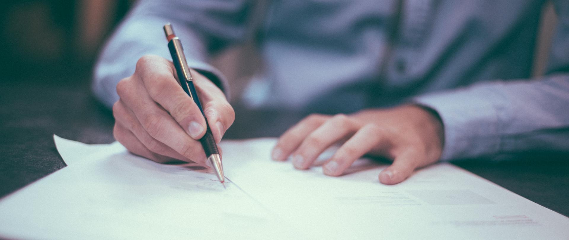 Na zdjęciu widoczny mężczyzna z długopisem w ręku oraz dokumentami.