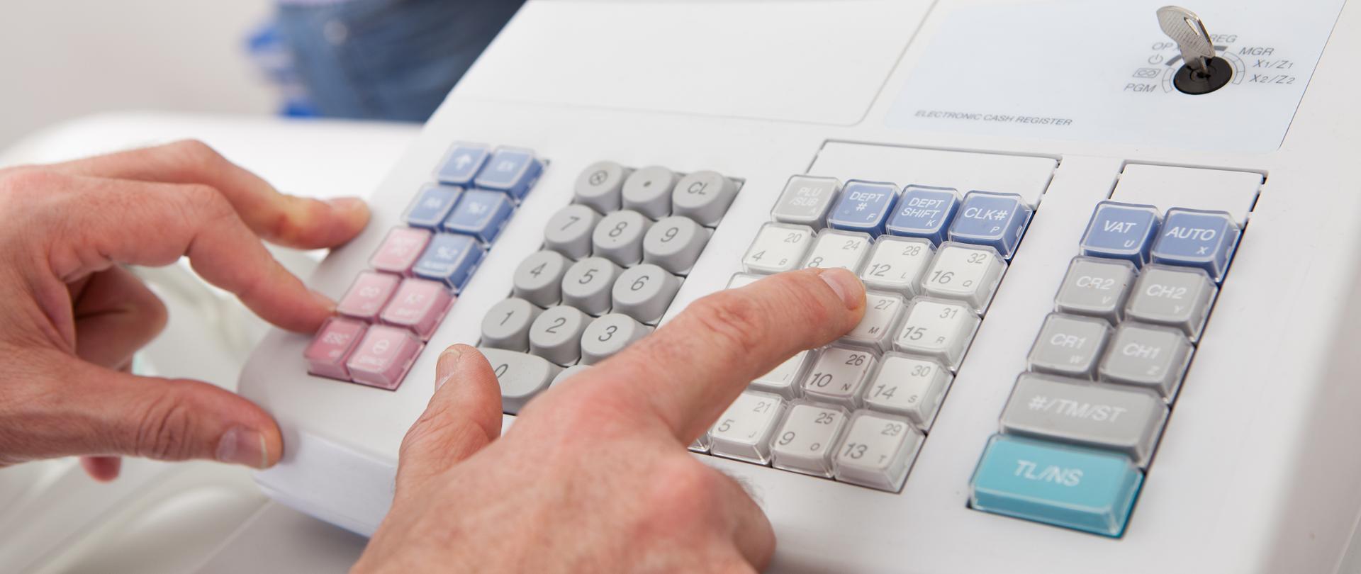 Sprzedawca naciska przyciski na kasie rejestracyjnej