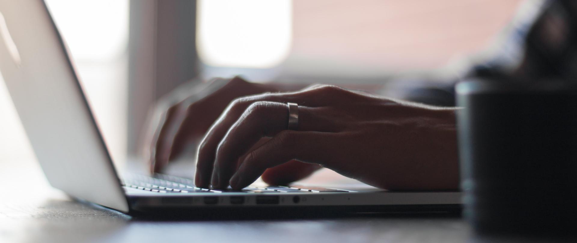 Na zdjęciu laptop na biurku, przy którym siedzi kobieta.