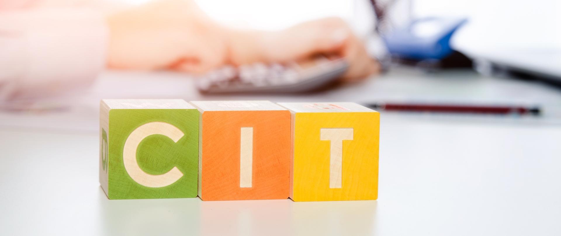 Kolorowe kostki z napisem CIT a w tle rozmyte dłonie i kalkulator
