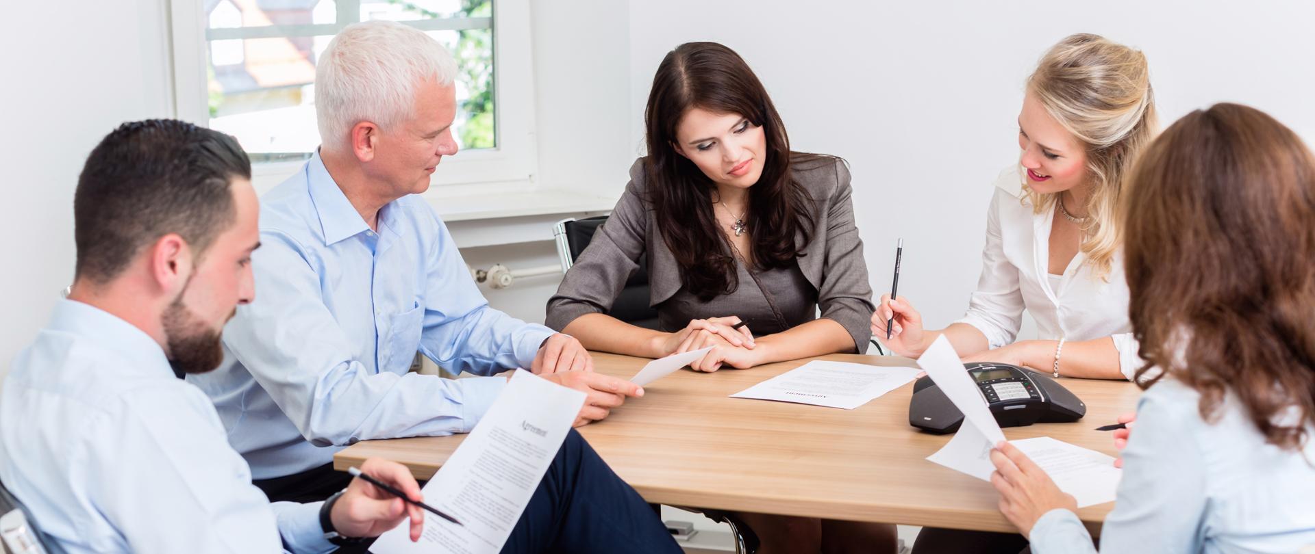 Pięć osób dyskutuje przy biurku przeglądając dokumenty