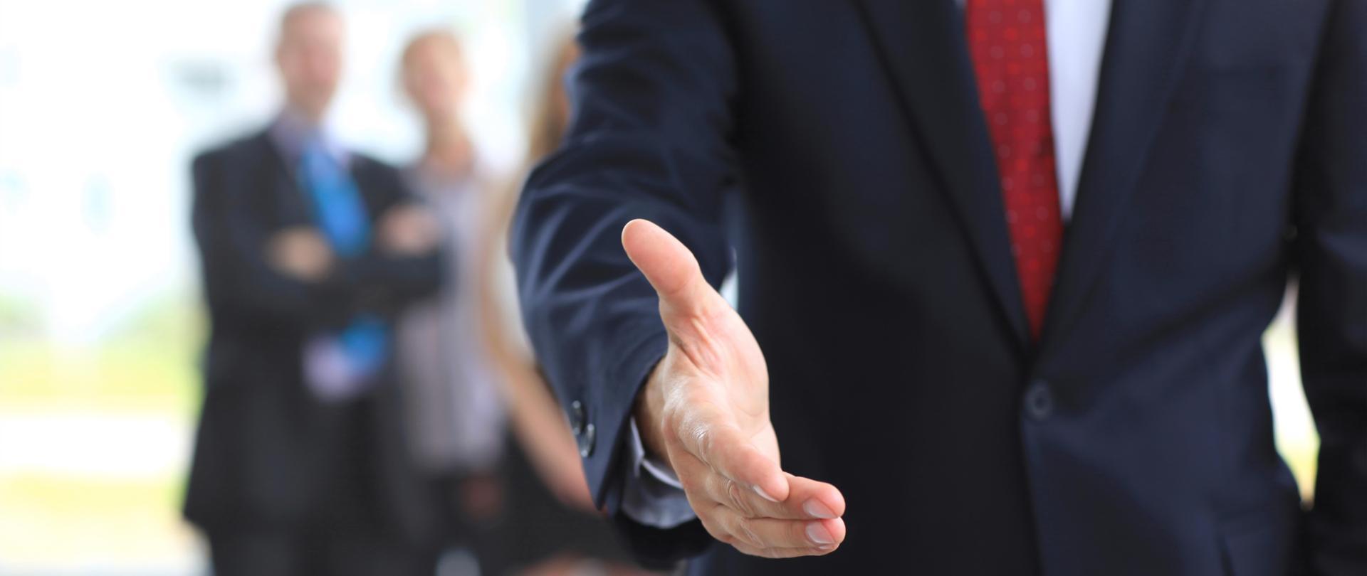 Wyciągnięta dłoń mężczyzny w garniturze a w tle trzy rozmyte postacie