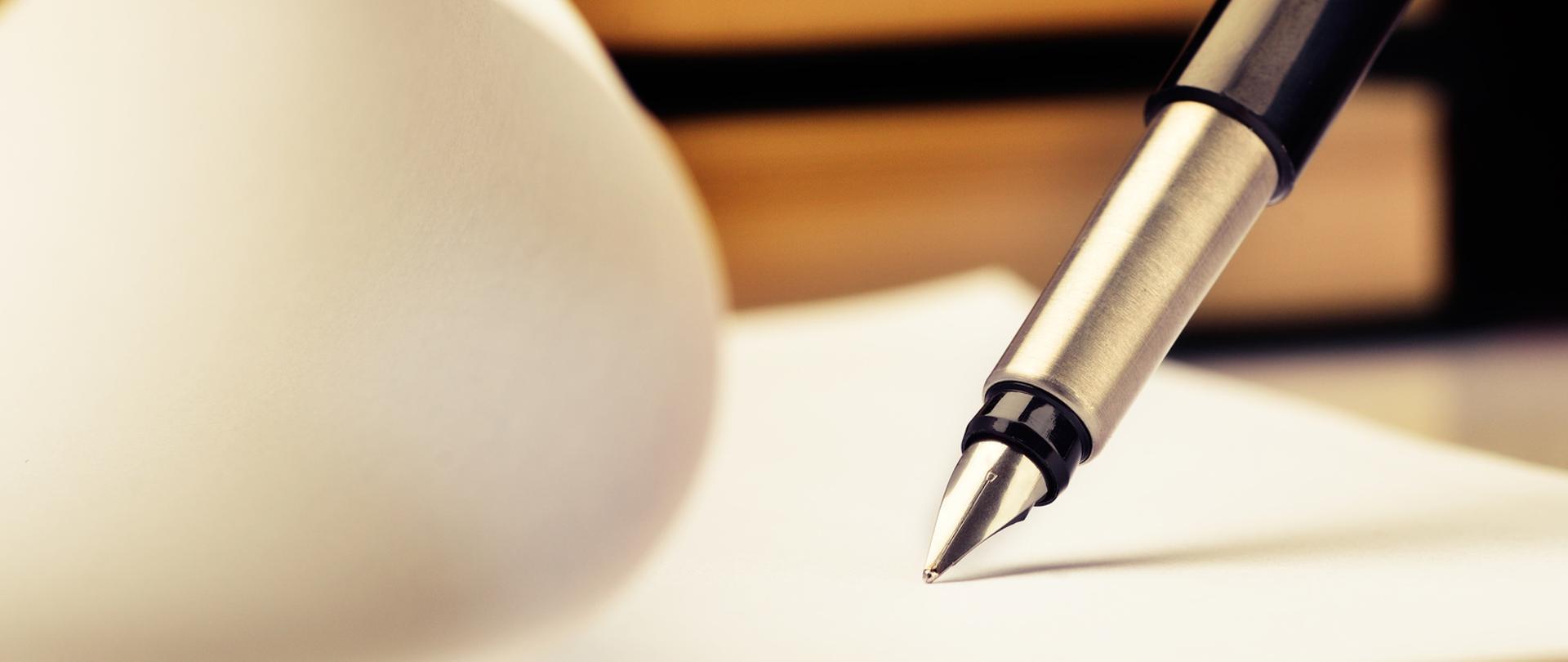 Pióro piszące na kartce papieru.