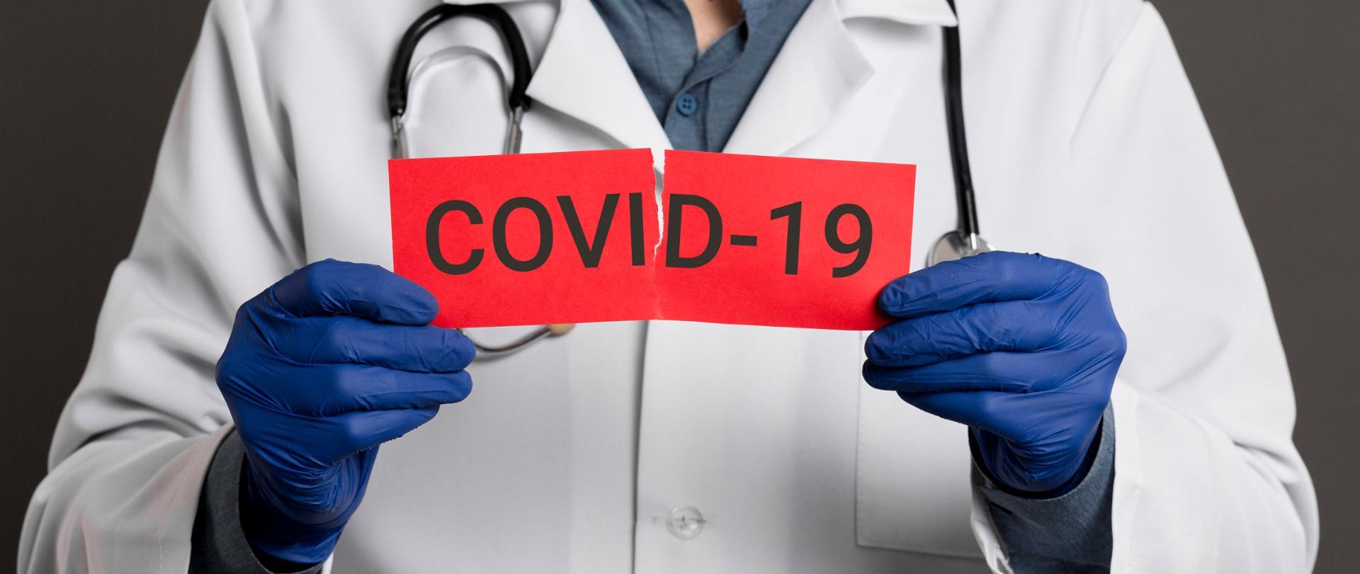Doktor trzymający kartkę z napisem COVID-19