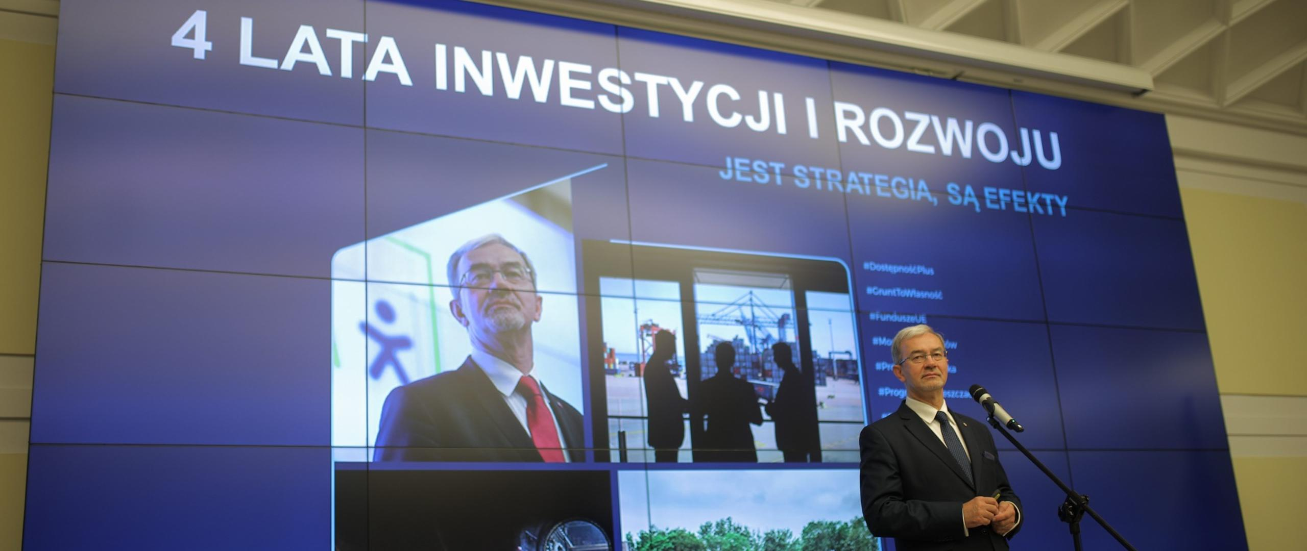 Minister Jerzy Kwieciński na scenie przy mikrofonie podczas konferencji, za nim ekran z grafiką ze zdjęciami związanymi z pracami ministerstwa oraz tytułem