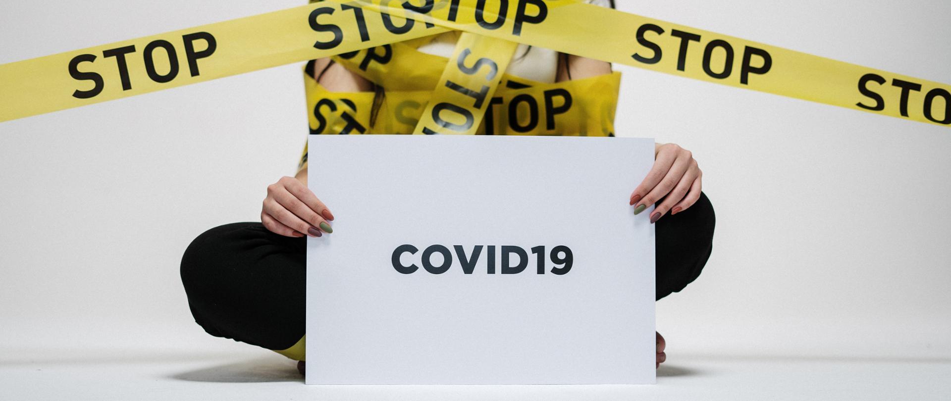 Sylwetka osoby siedzącej po turecku, w dłoniach kartka z napisem COVID19
