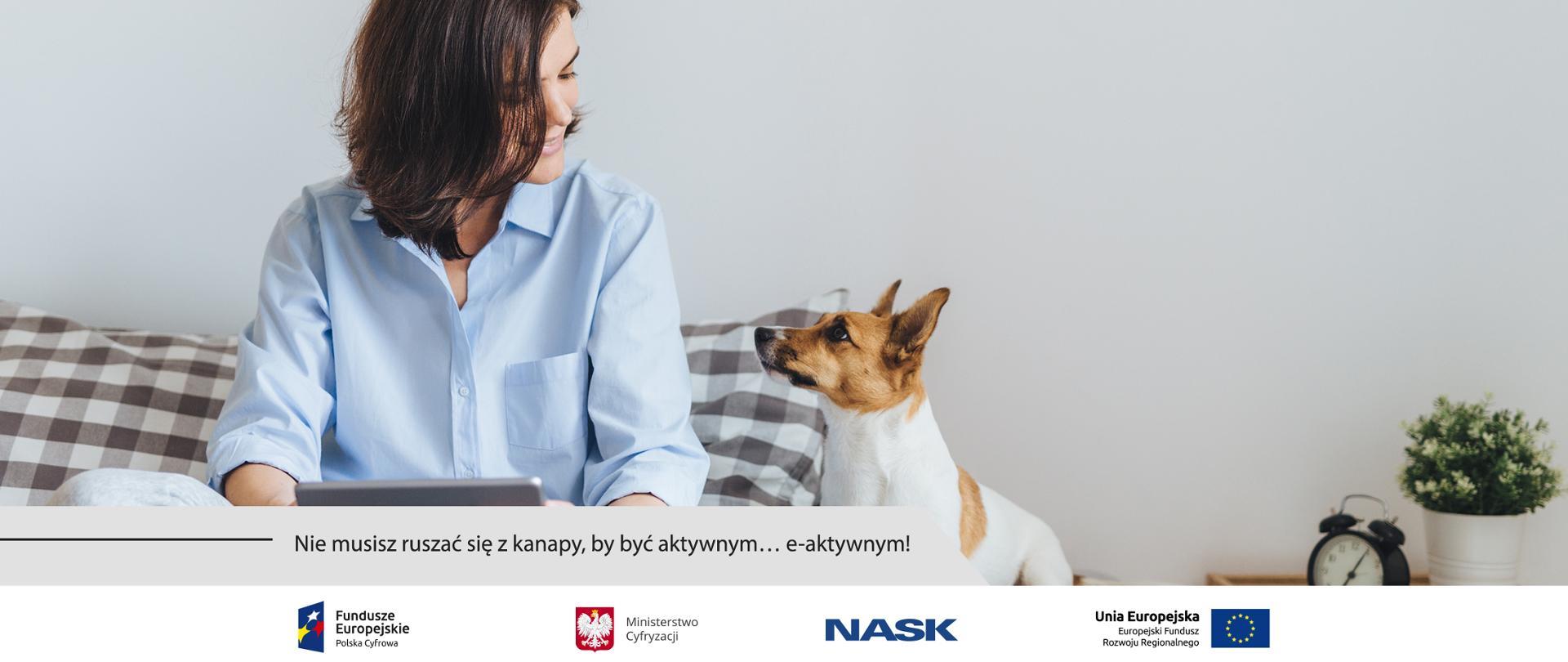Kobieta siedząca po turecku na łóżku z tabletem w rękach. Patrzy na siedzącego obok, wpatrzonego w nią psa rasy Jack Russel terrier.