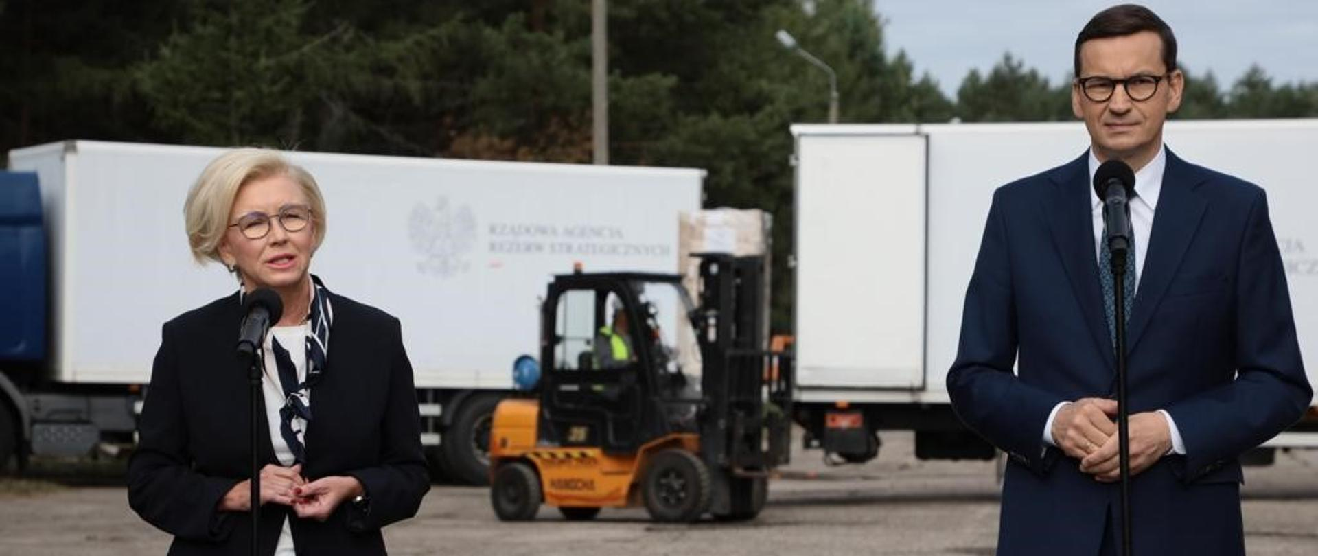 Premier Mateusz Morawiecki i wiceminister Marzena Machałek stoją przed mikrofonami, w tle samochody ciężarowe Rządowej Agencji Rezerw Strategicznych