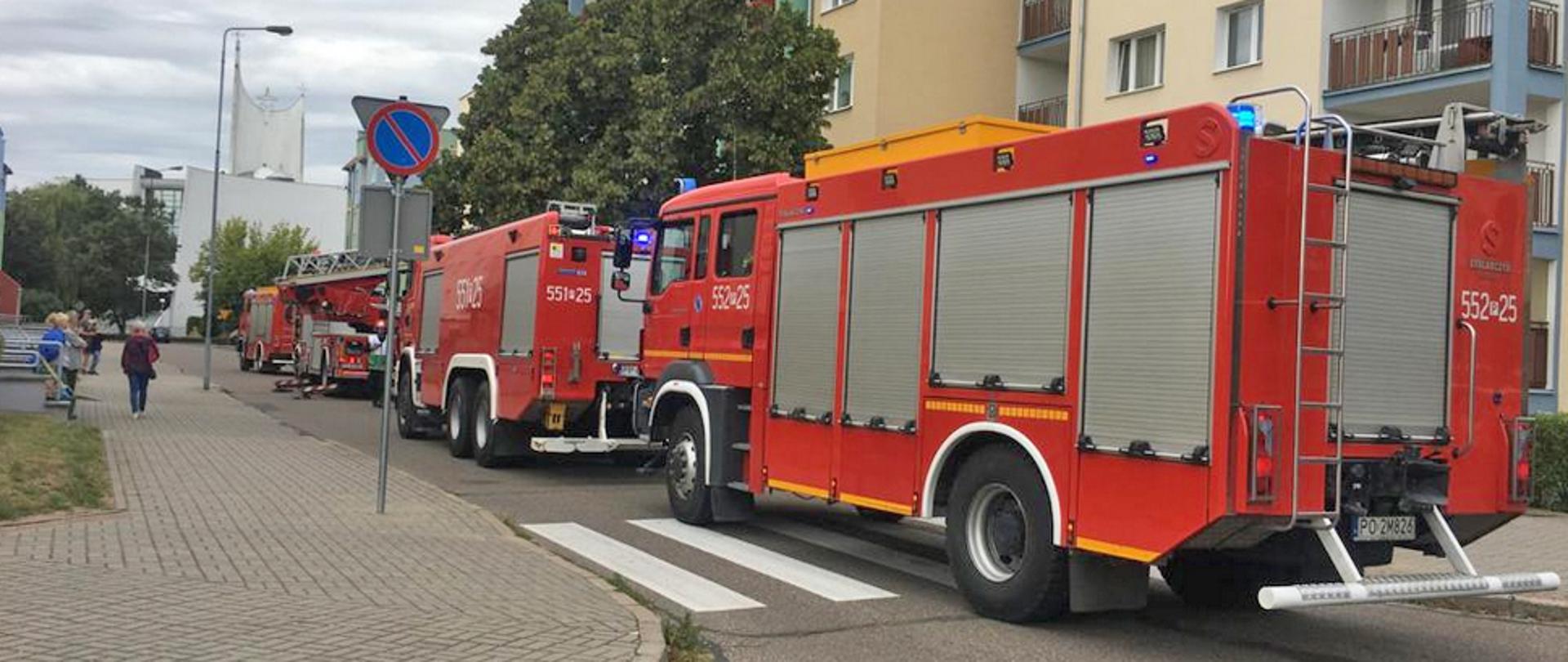 Na zdjęciu widnieją wozy strażackie podczas akcji gaszenia pożaru mieszkania w budynku wielorodzinnym. Dzień, jasno, bez opadów.